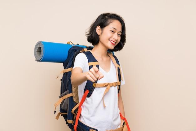 Aziatische reizigersvrouw over geïsoleerde puntenvinger bij u met een zekere uitdrukking