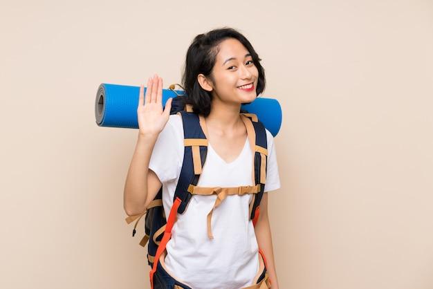Aziatische reizigersvrouw over het geïsoleerde achtergrond groeten met hand met gelukkige uitdrukking