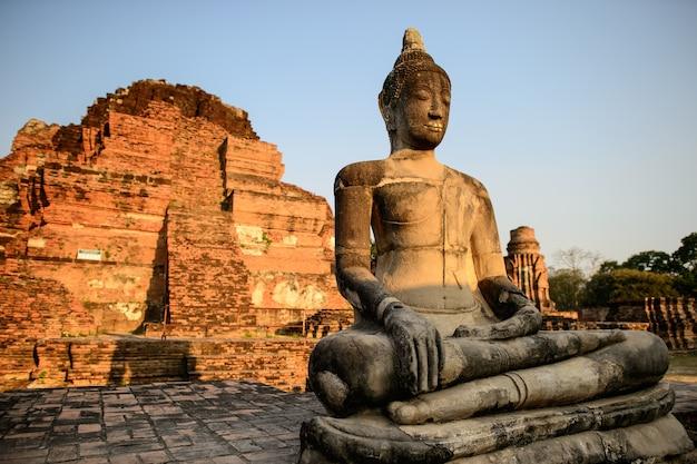 Aziatische religieuze kunst. oud zandsteenbeeldhouwwerk van boedha bij ruïnes. ayutthaya, thailand