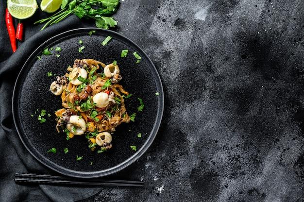 Aziatische roerbak noedels met inktvis en groenten. zwarte achtergrond