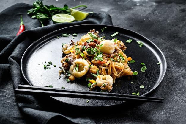 Aziatische roerbaknoedels met inktvis en groenten.