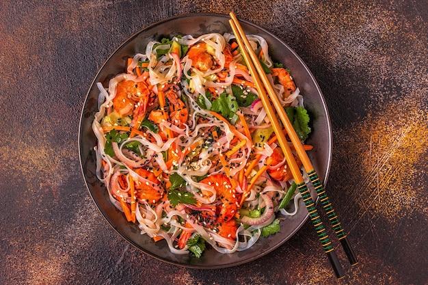 Aziatische salade met rijstnoedels, garnalen en groenten, bovenaanzicht.