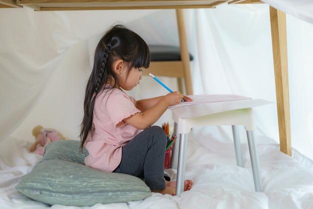 Aziatische schattig klein meisje tekening in papier liggend in een deken fort in de woonkamer thuis