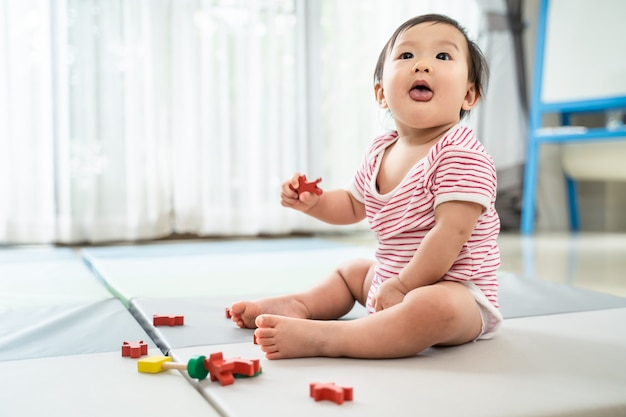 Aziatische schattige baby zitten en spelen een klein stuk speelgoed op zachte mat thuis.