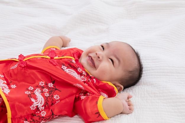 Aziatische schattige babyjongen chinese cheongsam kostuum peuter liggen op bed thuis glimlachen lachend goed gehumeurd, baby chinese nieuwsgierigheid jongen kind op zoek naar iets, gelukkig chinees nieuwjaar concept