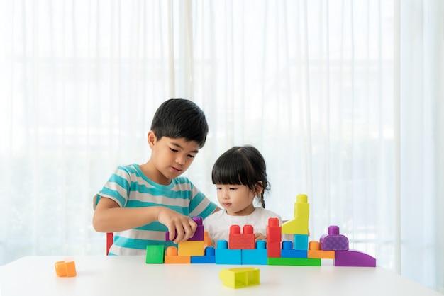 Aziatische schattige broer en zus spelen met een speelgoedblok ontwerper op de tafel in de woonkamer thuis.