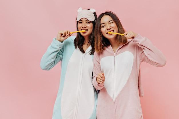 Aziatische schattige brunette meisjes in zachte pyjama's poetsen tanden
