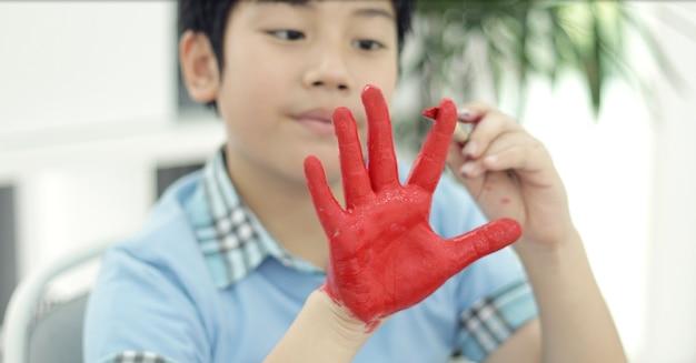Aziatische schattige kind schilderij waterkleur op je hand.