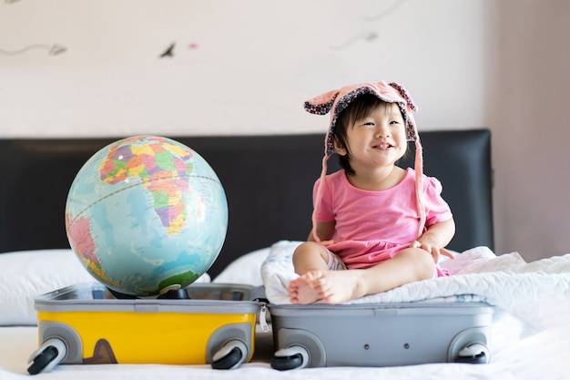 Aziatische schattige kleine baby meisje draagt hoed zittend op reistas met glimlach gevoel grappig en lachen op bed in de slaapkamer.