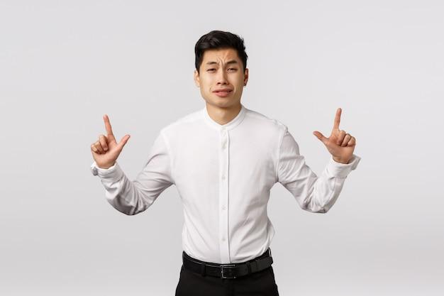 Aziatische schattige man die zich bang voelt, zich gedraagt als een lafaard of een dwaas persoon, die omhoog wijst, bezorgd grimassen, aarzelt en twijfels heeft, besluiteloos staat
