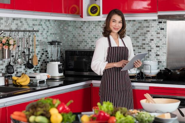 Aziatische schattige middelbare leeftijd vrouw in een schort stading met behulp van tablet-computer verbinding maken met internet in de keuken met een lachend gezicht en een vrolijke manier. concept voor moderne huisvrouwenlevensstijl.