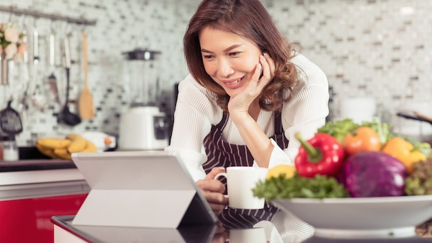 Aziatische schattige middelbare leeftijd vrouw met koffiekopje en met behulp van tabletcomputer verbinding maken met internet in de keuken met een lachend gezicht en een vrolijke manier. concept voor moderne huisvrouwenlevensstijl.