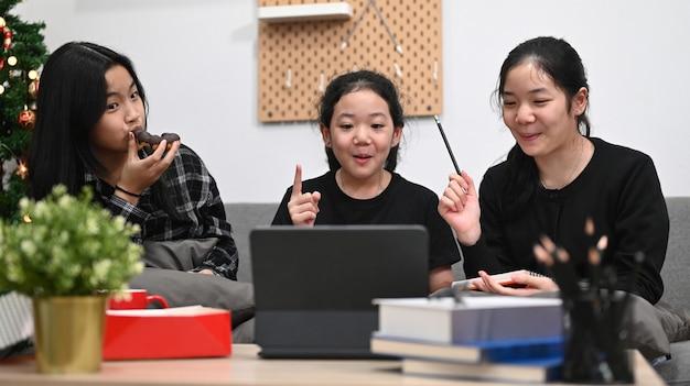 Aziatische schoolmeisjes die thuis samen online les studeren.