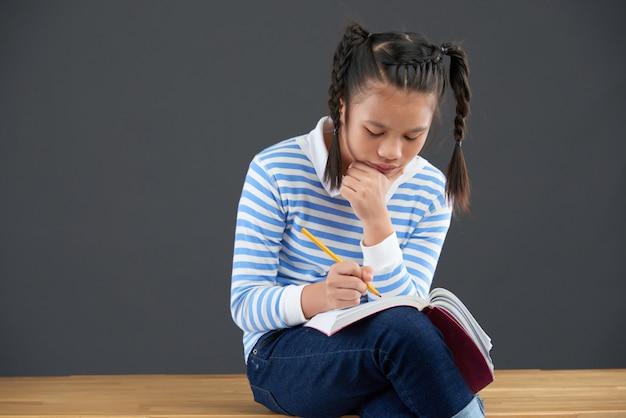 Aziatische schoolmeisjezitting op bureau, die in oefenboek met kin schrijven die bij hand leunen