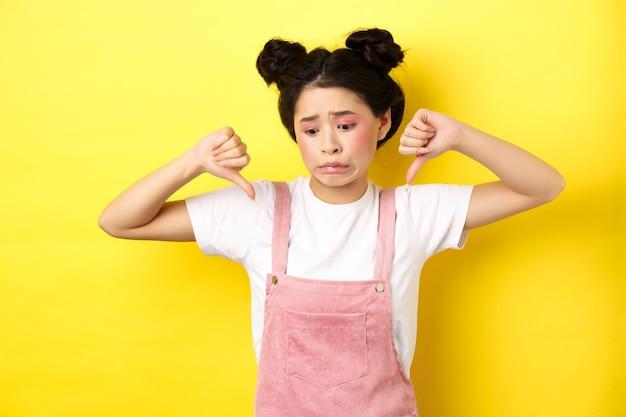 Aziatische schoonheid meisje ineenkrimpen van iets walgelijks, wegkijken en duimen naar beneden tonen om afkeer, negatieve emoties te uiten, staande in zomerkleding op gele achtergrond