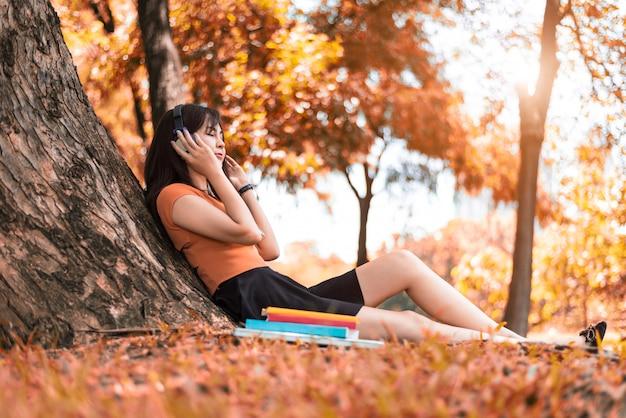 Aziatische schoonheid vrouw luisteren naar de muziek in park. people-levensstijlen en entertainment concep