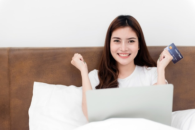 Aziatische schoonheidsvrouw gebruikt een creditcard om aankopen te doen met behulp van een computer via internet. met een blij lachend gezicht, een nieuw normaal online bedrijf zijn in de winkelervaring vanuit huis.