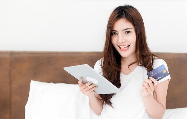 Aziatische schoonheidsvrouw gebruikt een creditcard om aankopen te doen met een tablet via internet. met een blij lachend gezicht, een nieuw normaal online bedrijf zijn in de winkelervaring vanuit huis.