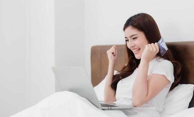 Aziatische schoonheidsvrouw gebruikt een creditcard om aankopen te doen via een computer via internet. met een blij lachend gezicht, een nieuw normaal online bedrijf zijn in de winkelervaring vanuit huis.