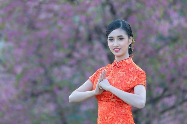 Aziatische schoonheidsvrouw met gebaar van gelukwens in chinees nieuwjaar
