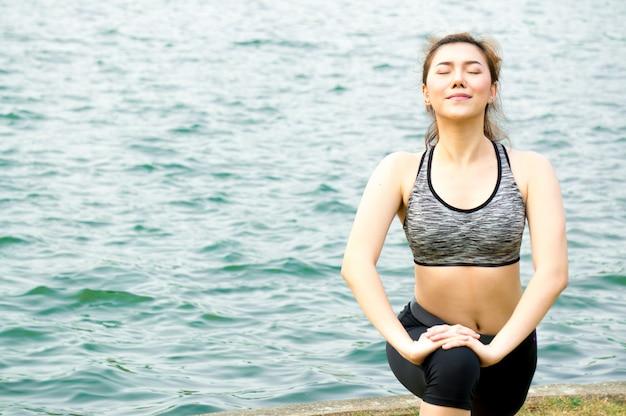 Aziatische schoonheidsvrouw oefening en het uitrekken zich door yoga in park