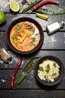 Aziatische schotel op een zwarte plaat op een houten tafel versierd met limoen, peper, zout, chili en bloem. smakelijke tom yam met rijst. restaurant serveren