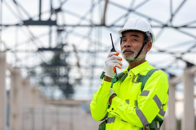 Aziatische senior ingenieur technicus kijken naar bouwcontrole bij de constructie van dakconstructies op constructie