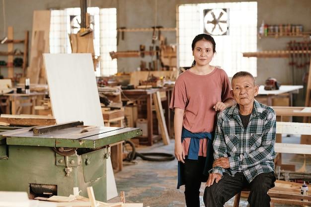 Aziatische senior man en zijn dochter werken in de werkplaats van een familietimmerman