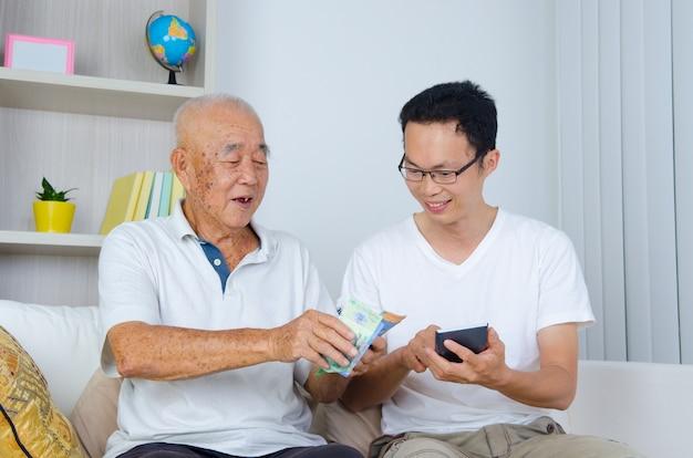 Aziatische senior man en zoon berekening van geld