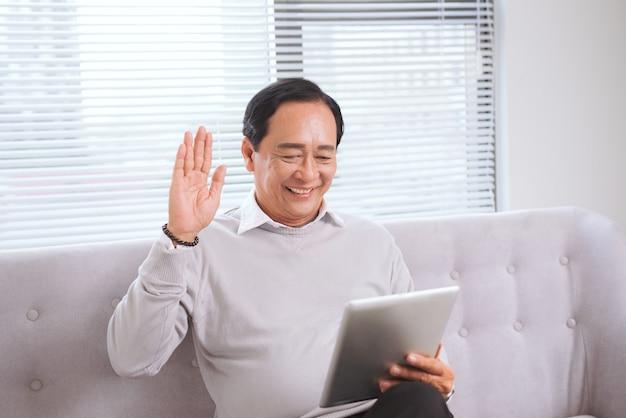 Aziatische senior man met tablet pc-computer maakt videogesprek