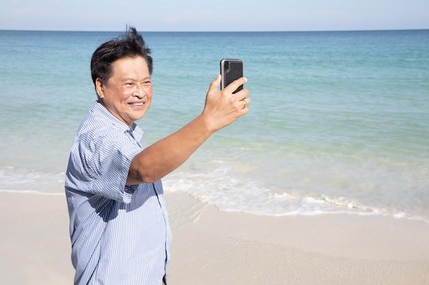 Aziatische senior man neemt selfie met mobiele telefoon op het strand