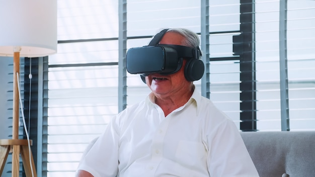 Aziatische senior man plezier spelen van videogame met virtual reality-bril thuis.
