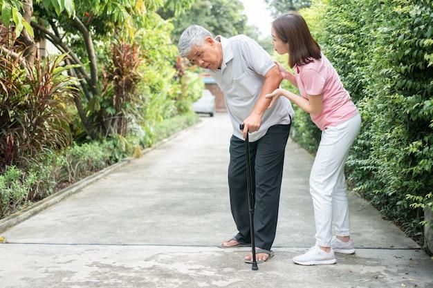 Aziatische senior man wandelen in de achtertuin en pijnlijke ontsteking en stijfheid van de gewrichten