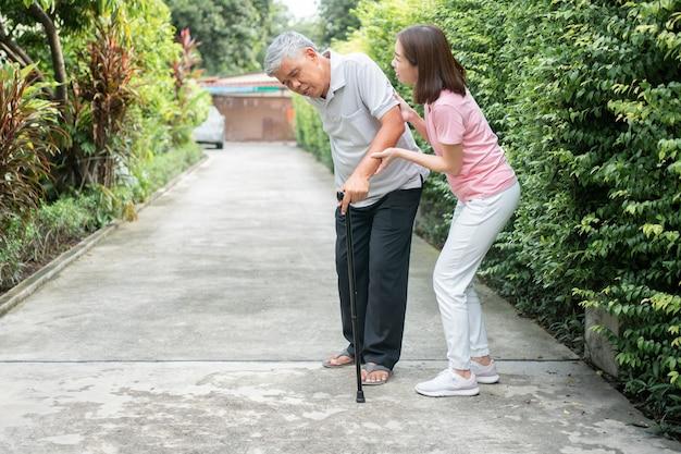 Aziatische senior man wandelen in de achtertuin en pijnlijke stijfheid van de gewrichten en de dochter kwam helpen ondersteunen.
