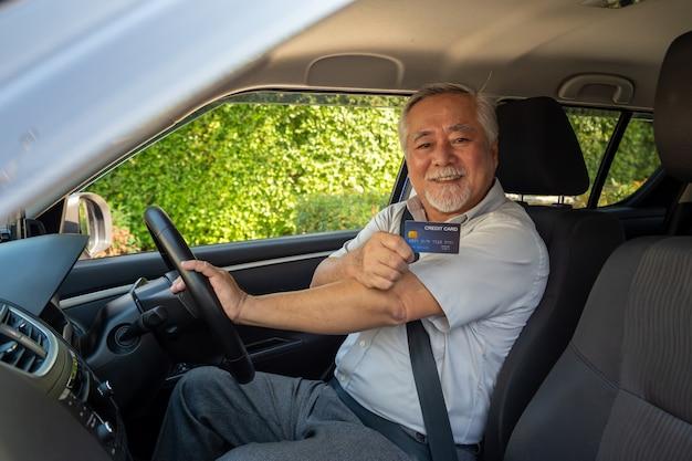 Aziatische senior man zit in de auto en creditcard te houden.