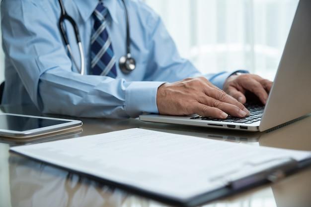 Aziatische senior mannelijke arts in blauw shirt met behulp van laptop.