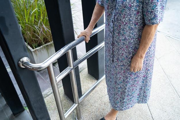 Aziatische senior of bejaarde oude dame vrouw patiënt gebruik helling loopbrug handvat beveiliging met hulp ondersteuning assistent in verpleegziekenhuis afdeling; gezond sterk medisch concept.
