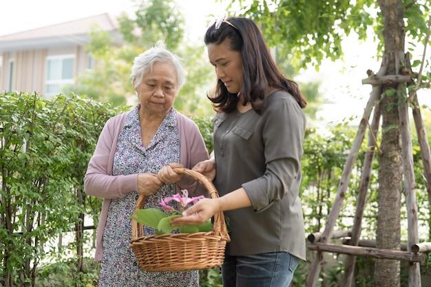 Aziatische senior of oudere oude dame die thuis voor het tuinwerk zorgt