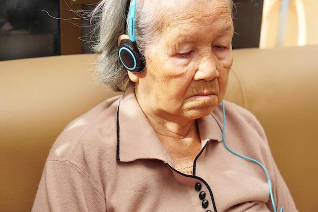 Aziatische senior of oudere oude dame vrouw geniet van het luisteren naar muziek