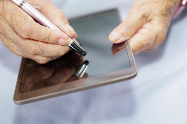 Aziatische senior of oudere oude dame vrouw met behulp van een stylus schrijven op tablet of tablet spelen op een blauwe doek. gezondheidszorg, medische technologie en modern concept.