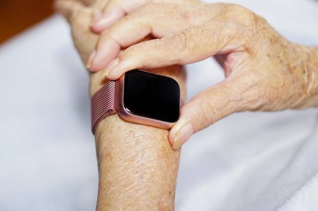 Aziatische senior of oudere oude dame vrouw met behulp van moderne slimme horloge