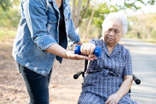 Aziatische senior of oudere oude dame vrouw oefenen met halter in park.