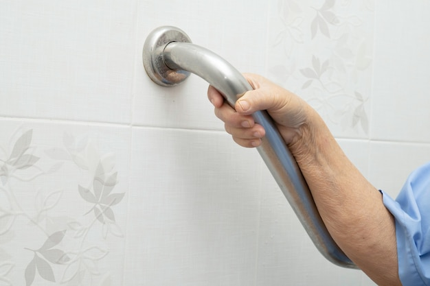 Aziatische senior of oudere oude dame vrouw patiënt gebruik toilet badkamer handvat beveiliging in verpleeg ziekenhuisafdeling, gezond sterk medisch concept.