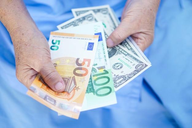 Aziatische senior of oudere oude vrouw van de dame geduldig bedrijf zorgen amerikaanse dollar euro bankbiljetten.