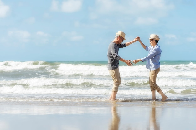 Aziatische senior paar dansen op het strand. helder huwelijksreis samen heel geluk na pensionering. plan levensverzekering. activiteit na pensionering in de zomer