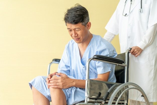 Aziatische senior patiënt rolstoel met kniepijn