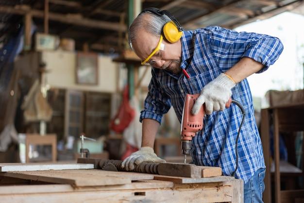 Aziatische senior timmerman met behulp van elektrisch boorgat in een houten plank in de timmerwerkplaats