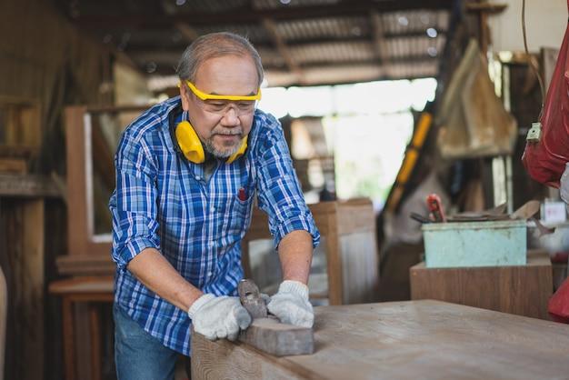 Aziatische senior timmerman met jointer vliegtuig passen oppervlak op houten tafel op de timmerwerkplaats