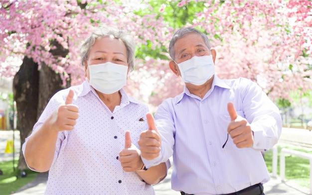 Aziatische senior vertrouwen gezond naar buiten gaan met gezichtsmasker in coronavirus pandemie. oude man en vrouw die een medisch masker dragen om covid-19 te beschermen bij nieuw normaal gedrag