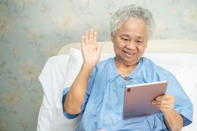 Aziatische senior vrouw met behulp van digitale tablet voor video-oproep social distancing concept